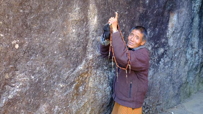Ein lokaler Bhutanese erklärt uns die Fuss- und Handabdrücke, welche in der Felswand zu sehen sind