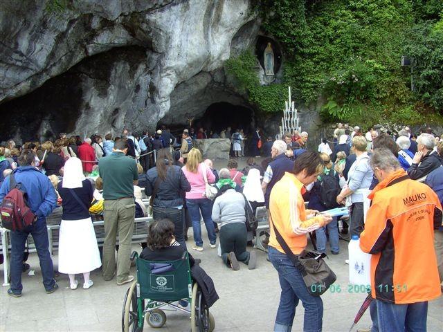 Peter Reicher vor der Hl. Grotte in Lourdes mit Oranger Regenjacke und Lourdes-Wasserkanister