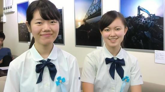 新出さんと佐藤さん。バックの写真は、「カメラマンがみた被災地・東北」の平林さんの作品です。