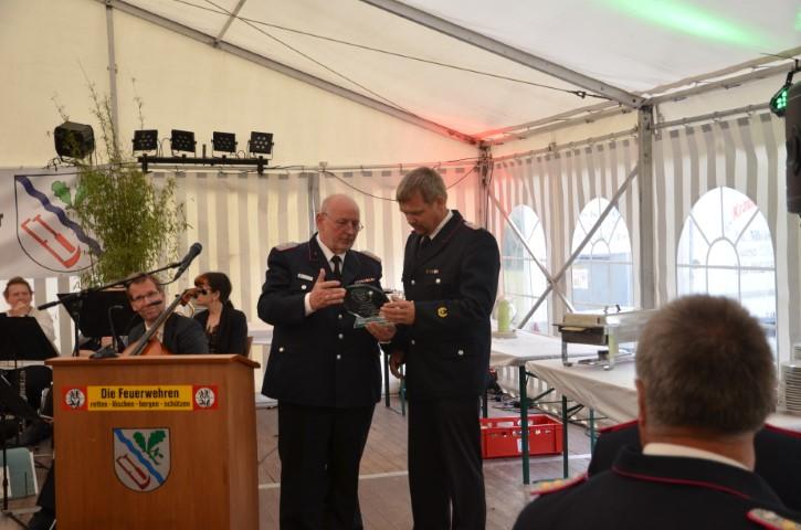 Der stellvertretende Kreisbrandmeister Bernd Waschnik überreicht das Geschenk des Kreisfeuerwehrverbandes Schleswig-Flensburg