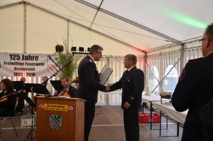 Der stellvertretende Landesbrandmeister Matthias Schütte gratuliert im Namen des Landesfeuerwehrverbandes