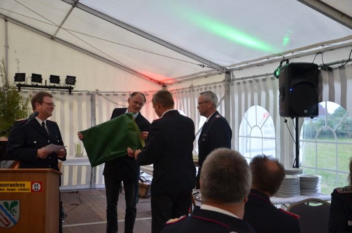 Die Wehrführung und der Bürgermeister der Nachbargemeinde Lürschau überreichen ihr Geschenk