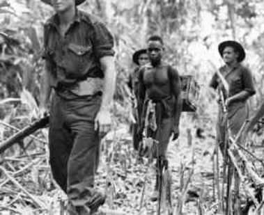 Een patrouille van Australische militairen in Nieuw-Guinea. De duiven worden vervoerd door een inboorling.