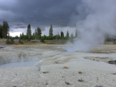 Aktiver West Thumb Geysir und Gewitterwolken