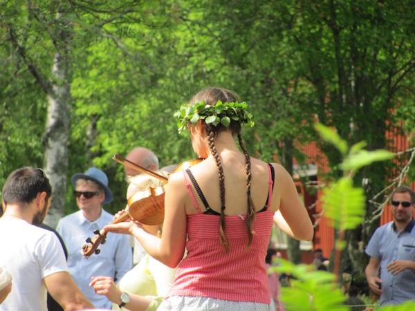 Frau mit Mittsommerkranz und Zöpfen spielt Geige, Schweden