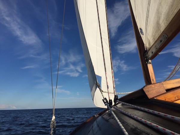 Holzboot, weiße Segel, blaues Meer, blauer Himmel