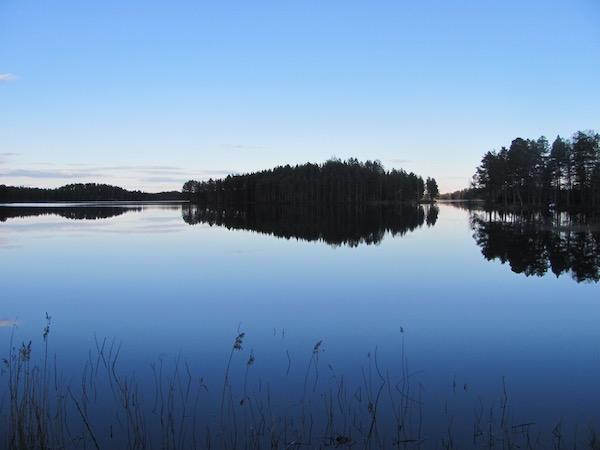 Großer See mit Insel und Spiegelung der Bäume im Wasser, Dalarna