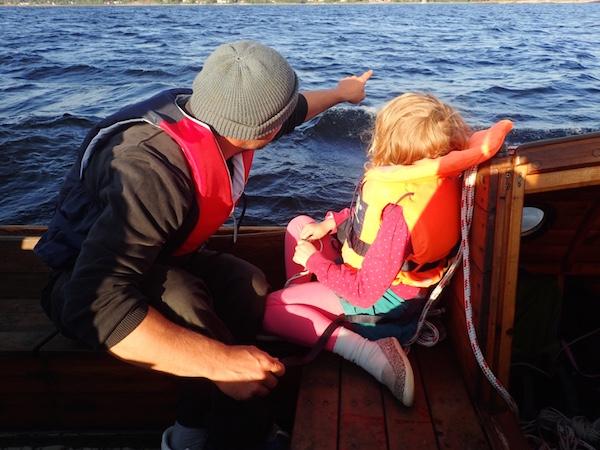 Mann und Kind segeln auf Holzboot