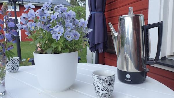 Schwedische Fika Szene: Rotes Holzhaus, Blümchen, Kaffeetassen und Nordica Kaffeekanne