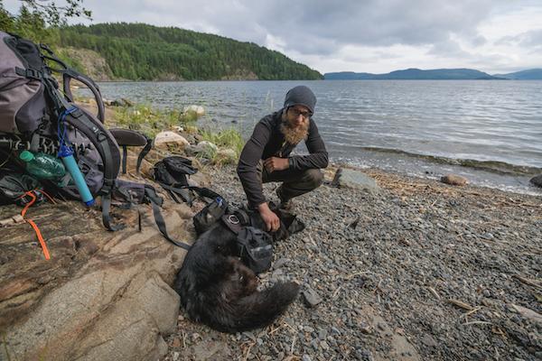 Backpacker mit Hund am Meer an der Hohen Küste in Schweden