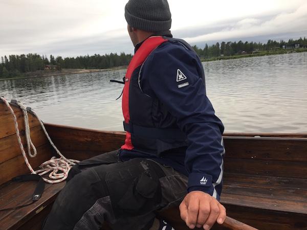 Mann am Ruder eines Holzboots, Nordschweden