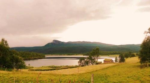 Schwedische Landschaft: Wiesen, See, Hütte und Wolken