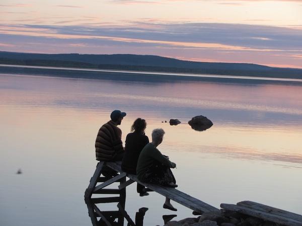 Drei Menschen am Steg in der Mitternachtssonne