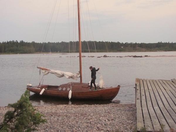 Mitternachtssonne in Schweden, Frau auf Segelboot aus Holz, Weiße Nächte in Skandinavien
