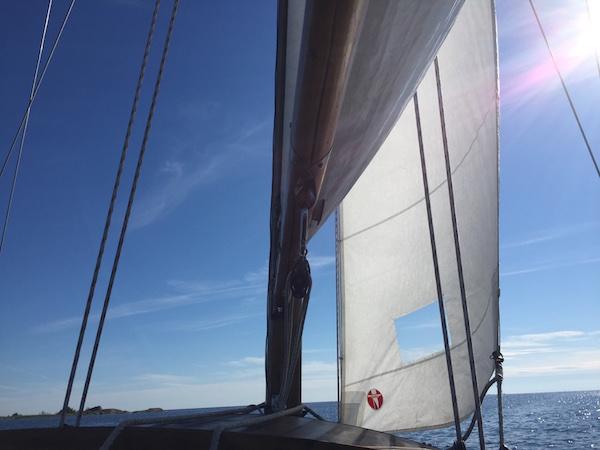 Holzboot mit weißen Segeln auf blauem Meer vor blauem Himmel