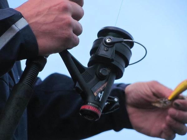 Nahaufnahme eines Anglers: Hände, Spule, Wobbler