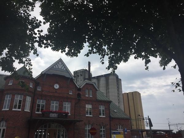 Historisches Bahnhofsgebäude in Sölvesborg, Schweden mit Fabrik im Hintergrund