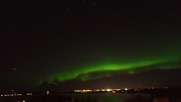 Sternenhimmel, Umeå und Meer mit grünen Polarlichtern