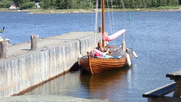 Holzboot am Steg und Mann der sich sonnt