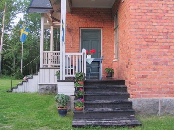 Rotes Backsteinhaus mit Blumen und Schwedenflagge auf Norrbyskär