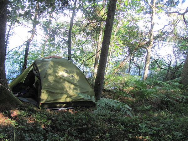 Grünes Zelt im Wald direkt an einem See in Schweden