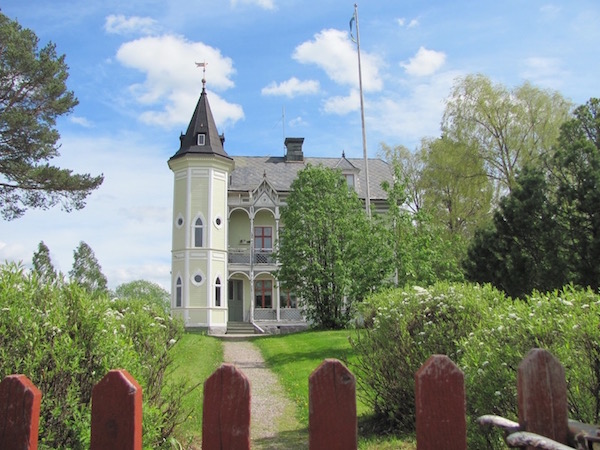 Schickes weiß-beiges Haus mit Türmchen, Flaggenmast, rotem Holzzaun und schönem Garten, irgendwo in Mora, Dalarna, Schweden