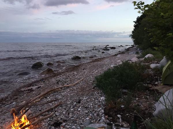 Zelt und Lagerfeuer am Meer mit Steinstrand