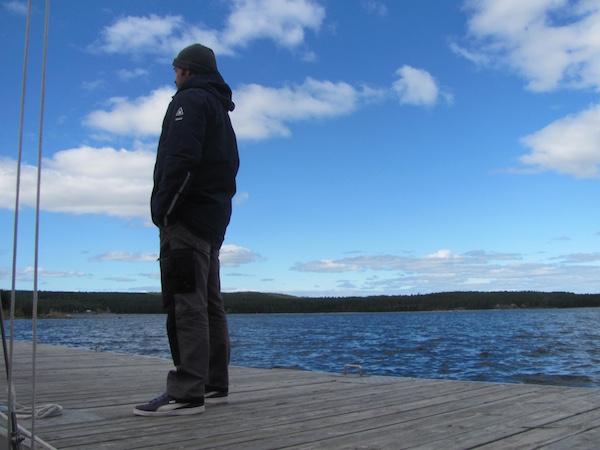 Mann in Gaastra Jacke Reach auf Holzsteg mit blauem Himmel und blauem Meer