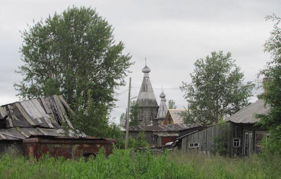Blick auf kleine Hütten, mit Kems Holzkirche im Hintergrund