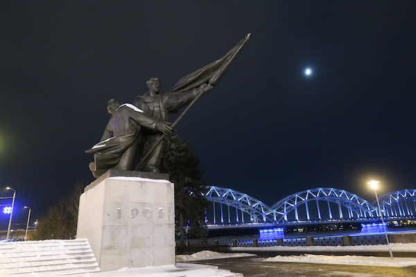 Revolutionsdenkmal 1905 in Riga bei Nacht mit angestrahlter Brücke im Hintergrund