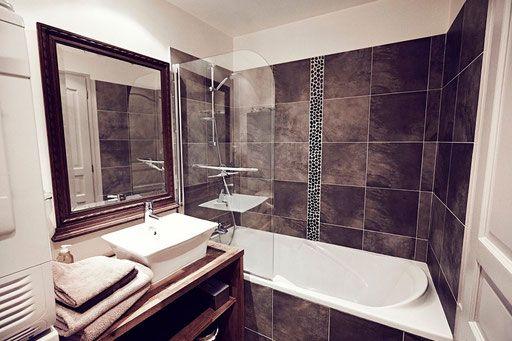 La salle de bain avec baignoire et douche