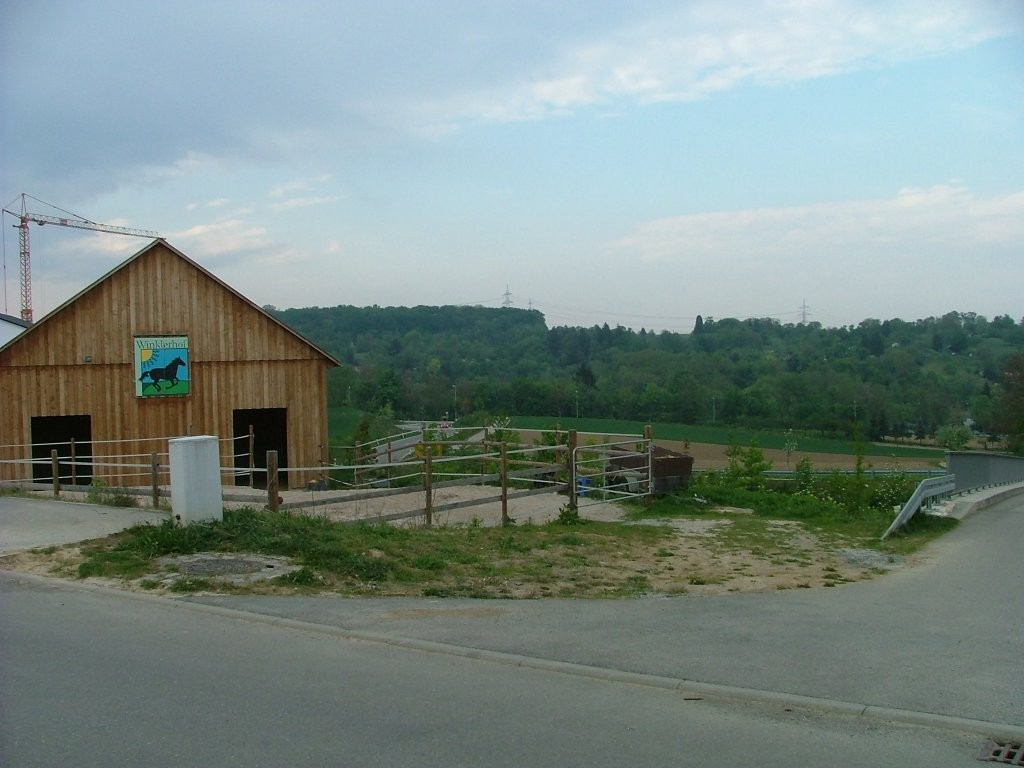 Am Ortseingang überqueren Sie die neue Umgehungsstraße. Beim Blick zurück ist der Reiterhof Winklerhof zu sehen und im Hintergrund der Rotenackerwald, wo auch ein Naturfreundehaus steht.