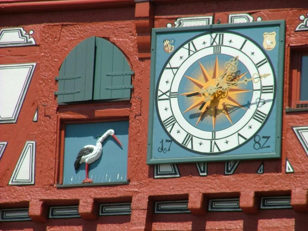 Uhr und Storch in der Fasade des Rathauses.