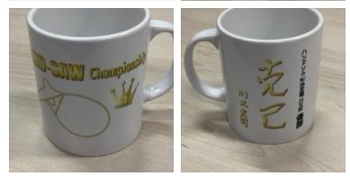 優勝賞品の特製マグカップ。川又先生の座右の銘「克己」の直筆データがプリントされています。