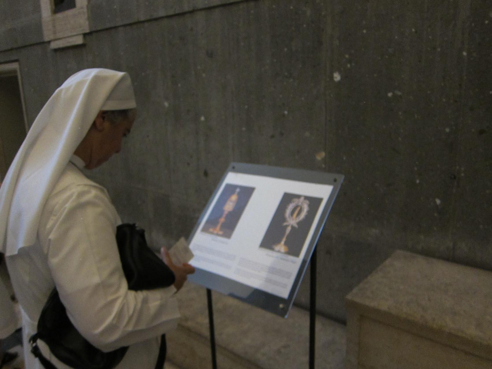 祭壇の後ろに安置されている聖遺物の解説を見るシスター