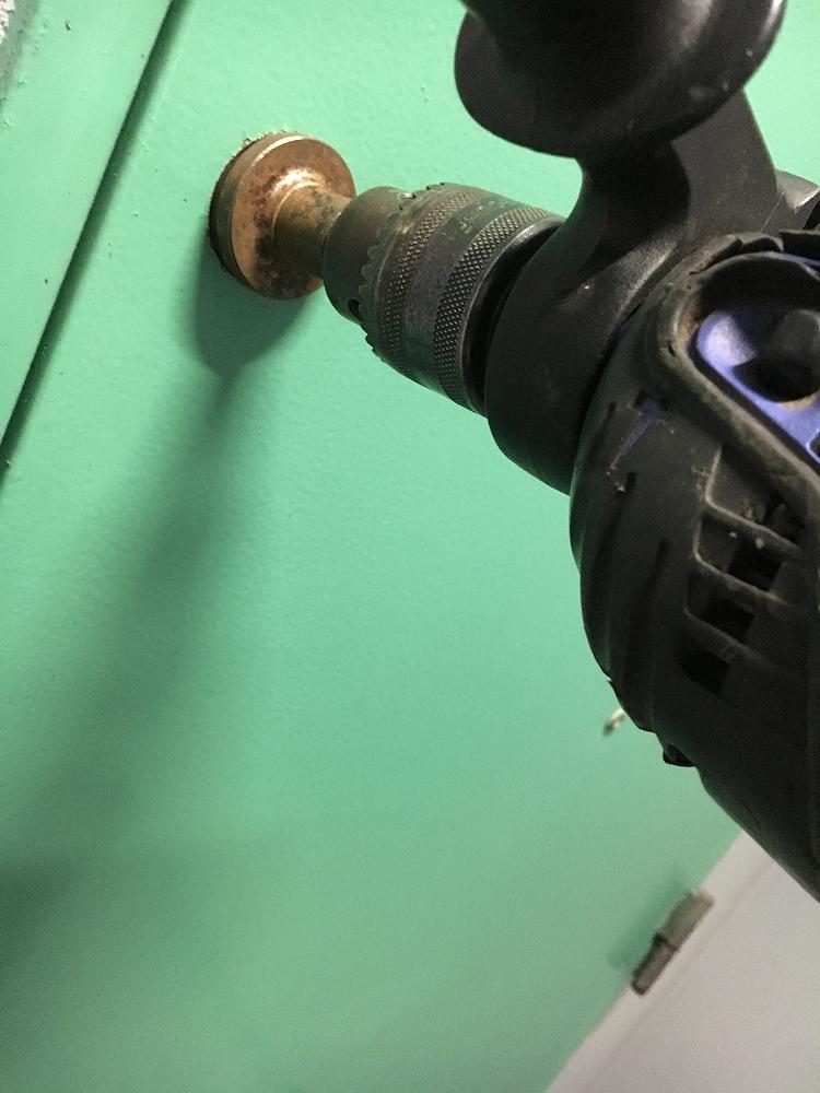 ドリルで鉄扉に穴をあけている