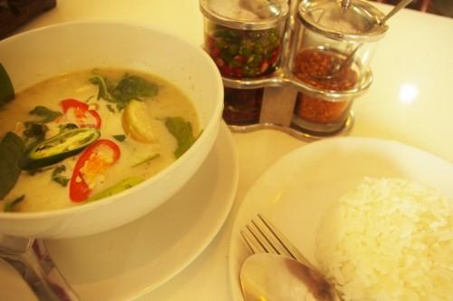 レストランで食べた、本場タイのタイ・カレー。グリーンカレーの写真。テーブルの上の左側にグリーンカレー。唐辛子などの具材、薬味が入っている。右側にはタイのお米、ライスが白いお更に盛り付けてある。中央には乾燥タイプの唐辛子、生タイプの唐辛子の調味料入れも映る。[タイ・バンコク旅行(出張)写真ブログの画像]