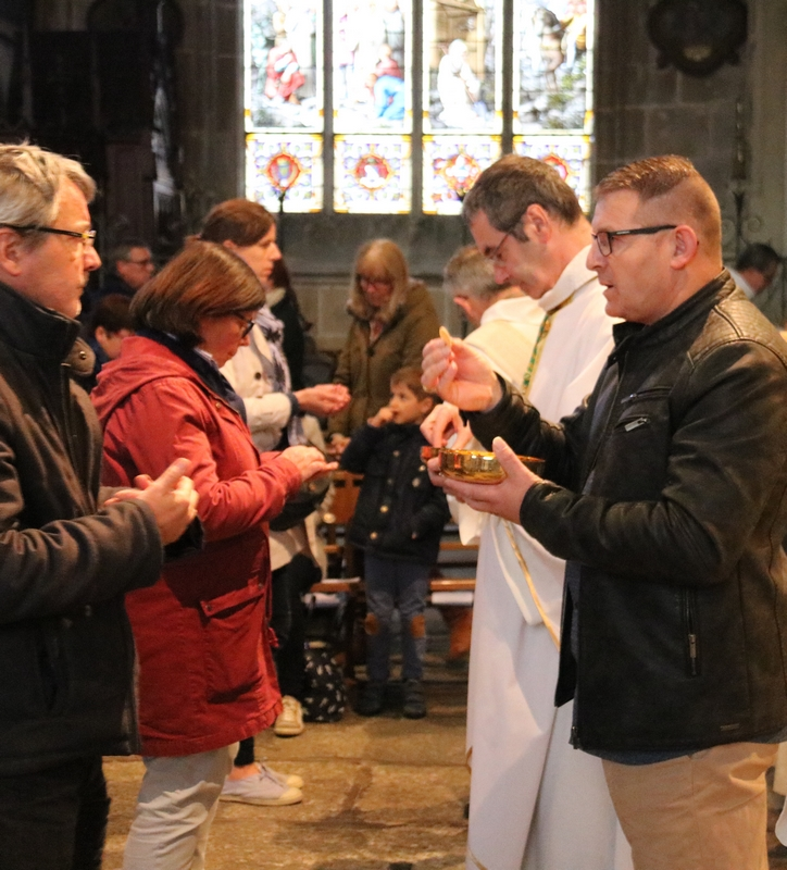 Joseph distribue la communion à l'assemblée des fidèles