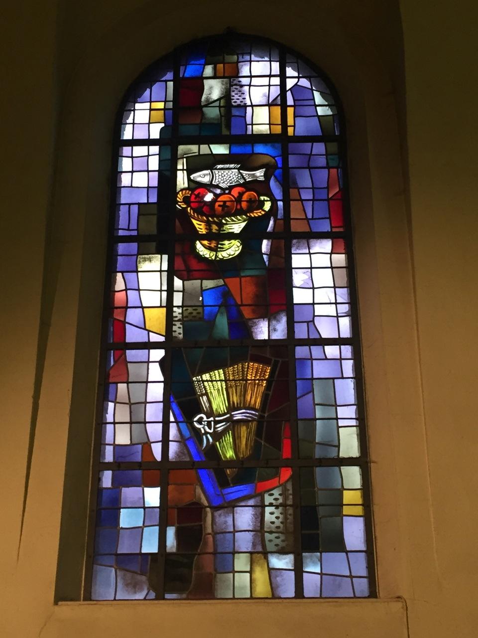 Le miracle de la multiplication des pains et des poissons ; derrière c'est l'Eucharistie qui est suggérée.