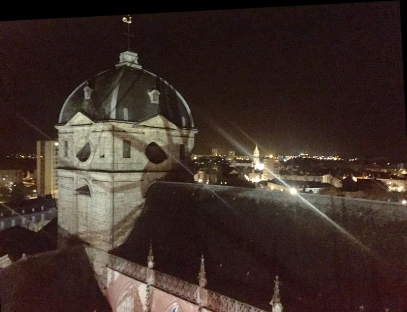 Derrière le clocher de la basilique, l'église St Pierre de Montsort illuminée