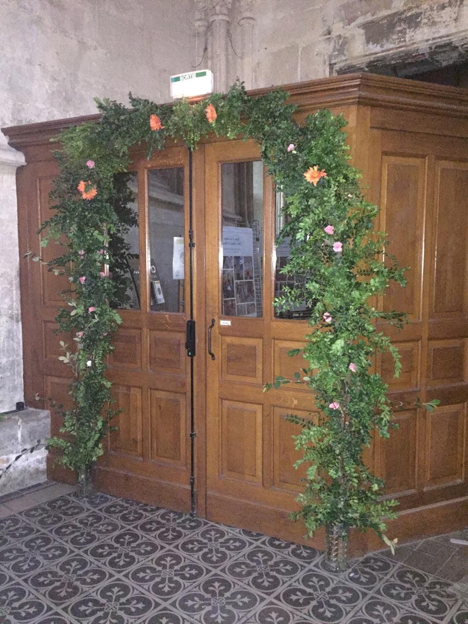 On peut admirer la décoration de la porte sainte. Merci à nos fleuristes !