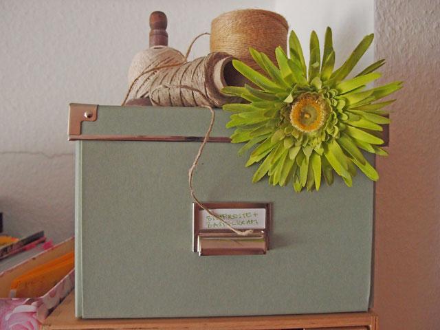 Schachtel mit grüner Blume, Mentallbeschlägen und Garnrollen auf einem Schrank neben Ordnern