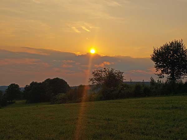 abendsonnenstrahl zwischen wolken auf einer wiese der schwäbischen alb