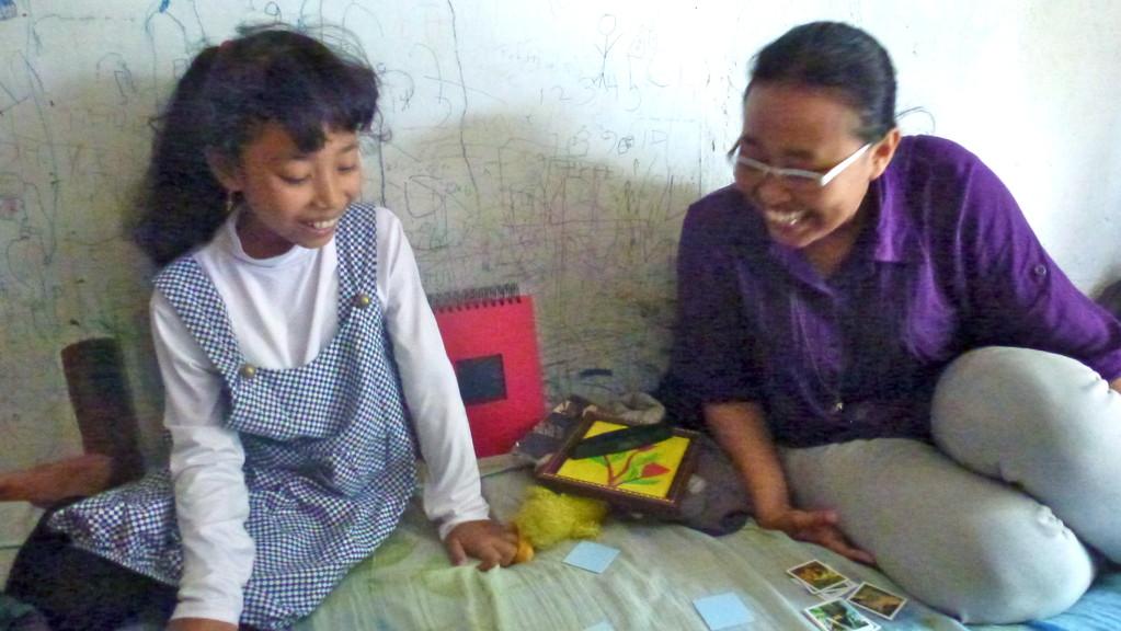 """Memory - für Riris ein ganz neues Spiel. Daneben unsere Übersetzerin und Riris Mentorin. Sie war selbst ein Projektkind und hat es durch diese Unterstützung geschafft zu studieren. Heute ist sie Lehrer-Assistentin und wird bald """"richtige"""" Lehrerin sein."""