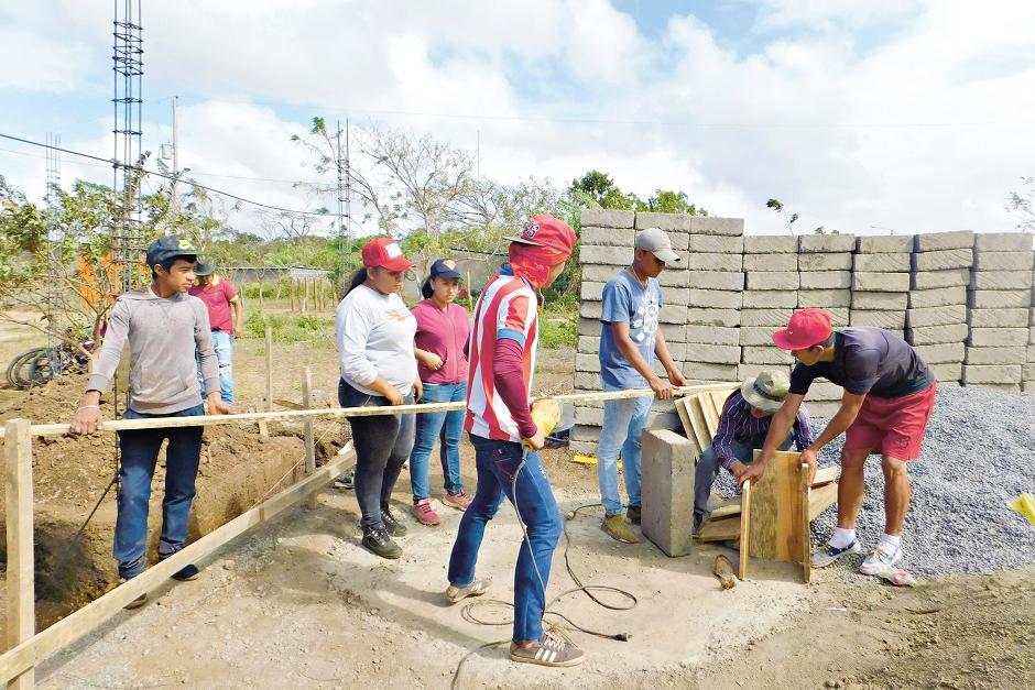 Zwei ältere Auszubildende weisen die Neulinge in verschiedene Bauarbeiten ein. Das Foto entstand zu Beginn der Ausbildung.