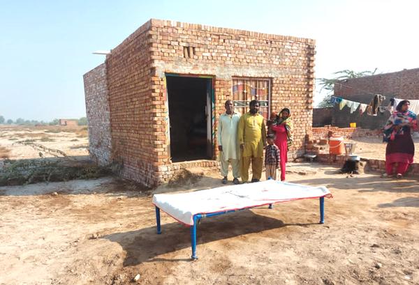 Rashid Masih (links), sein Sohn Vishal und dessen Familie stehen stolz vor ihrem kleinen Haus. Heute führen sie ein einfaches, aber gutes Leben.