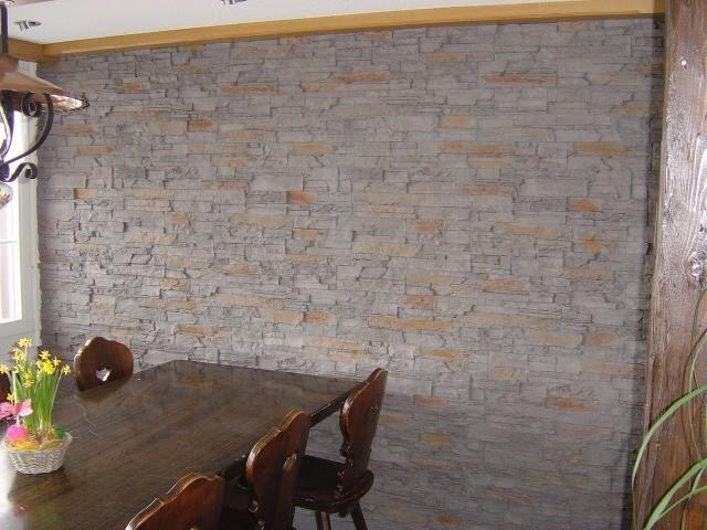 Die Wand und die dunkeln Möbel gleichen einem Rustico