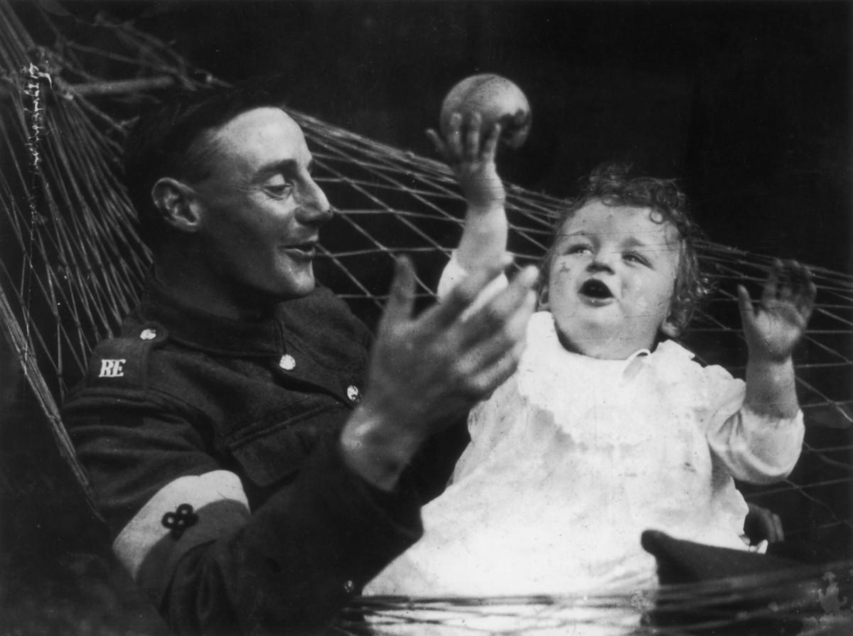 1919. Soldado británico jugando con su hija, nacida durante la guerra...