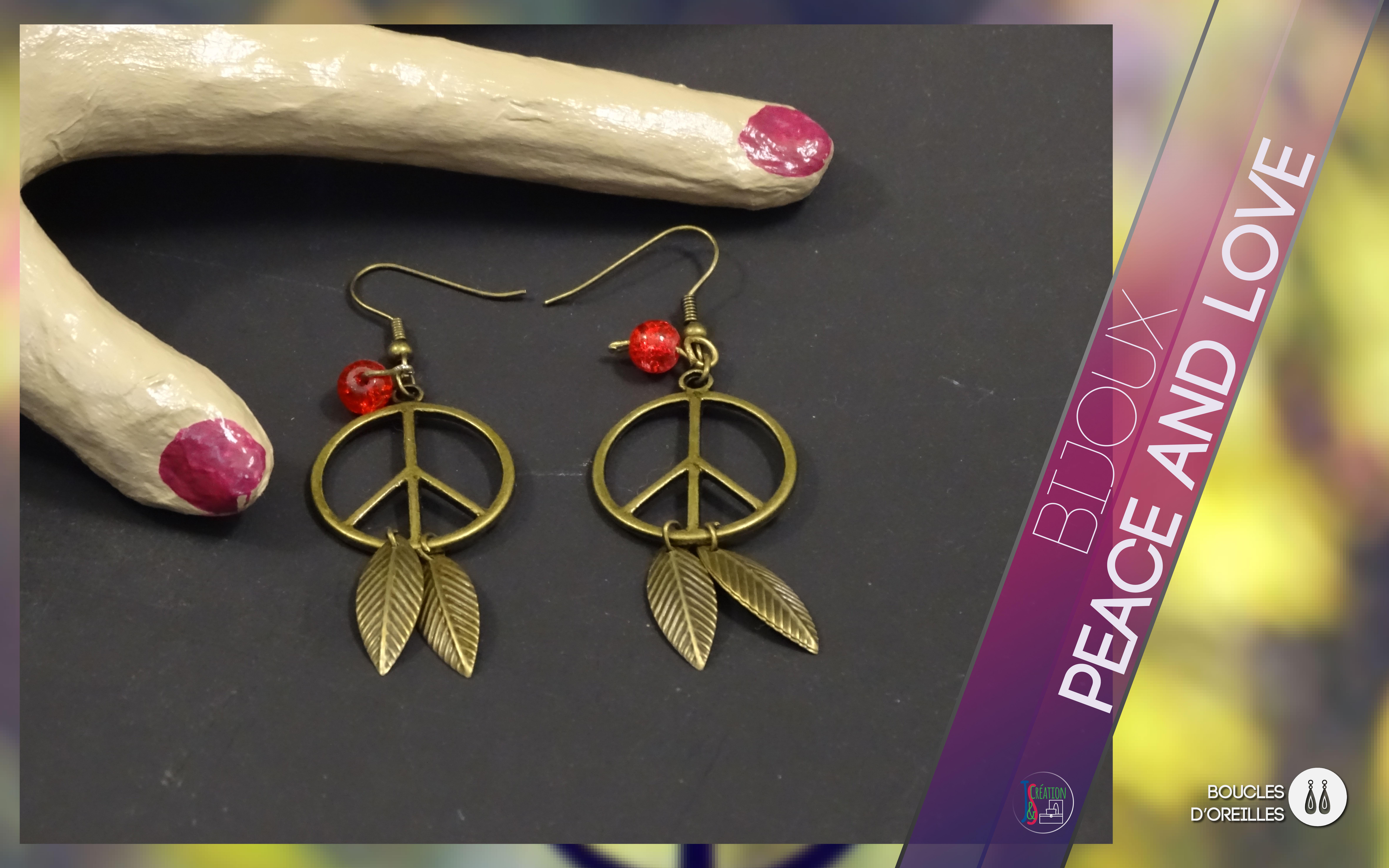 Peace and Love Boucles d'oreilles Boucles d'oreilles en forme du symbole Peace and Love ornée de plumes en breloque et de perles.