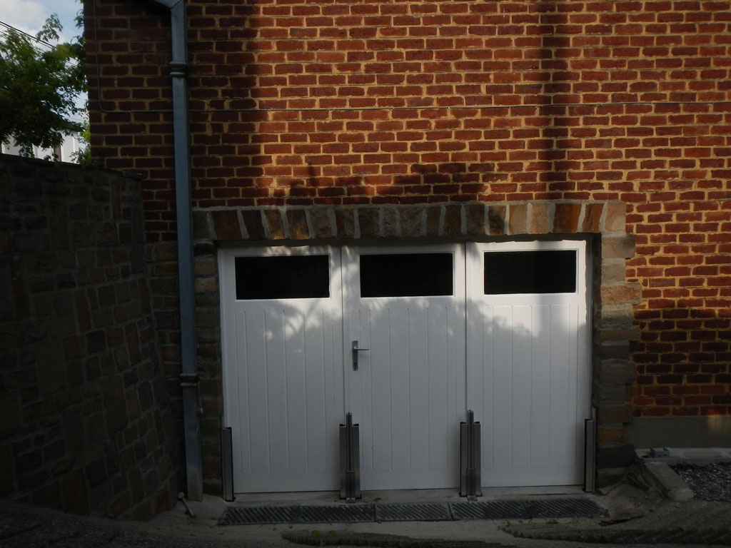 Protection crue  accès garage en contrebas qui montre l'installation des poteaux intermédiaires haute résistance en aluminium, avant de positinner les panneaux amovibles étanches.